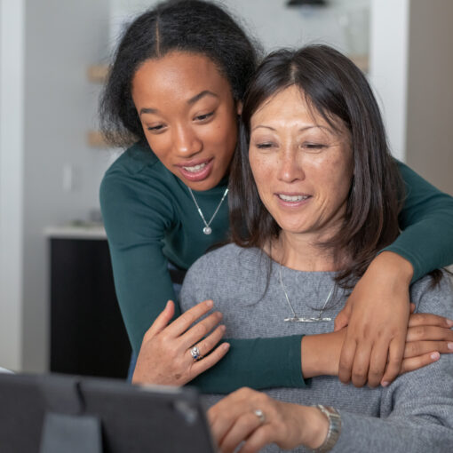 A beautiful mixed race teenager affectionately embraces her mother as they use a tablet computer to visit and stay connected with family and friends while isolating at home during the Covid-19 pandemic. Social distancing, mental health, and social teleconferencing concepts.